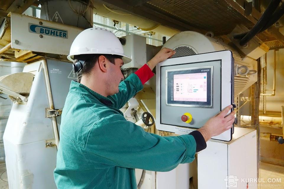 Робітник заводу настроює обладнання Bühler