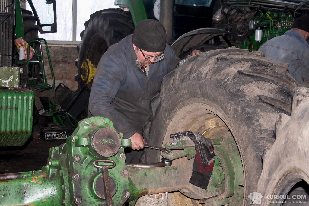 Олександр  Кащук налаштовує розвал-сходження коліс трактора John Deere 8400