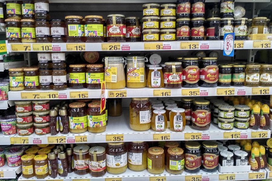 Різноманіття видів меду, з різною упаковкою на полицях одного з супермаркетів Польщі