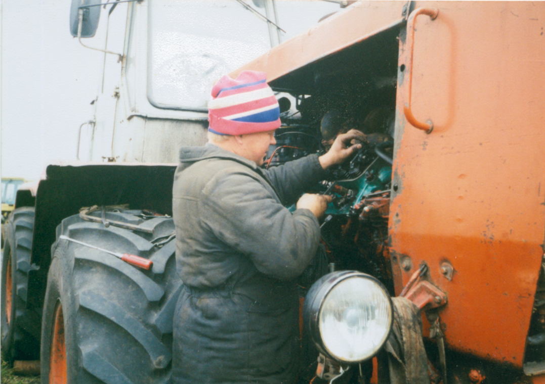 Олександ Подоляка ремонтує трактор, середина 90-х років